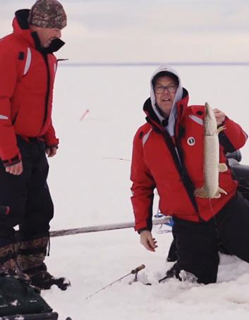 Un pêcheur sort un brochet appâté sous la glace.