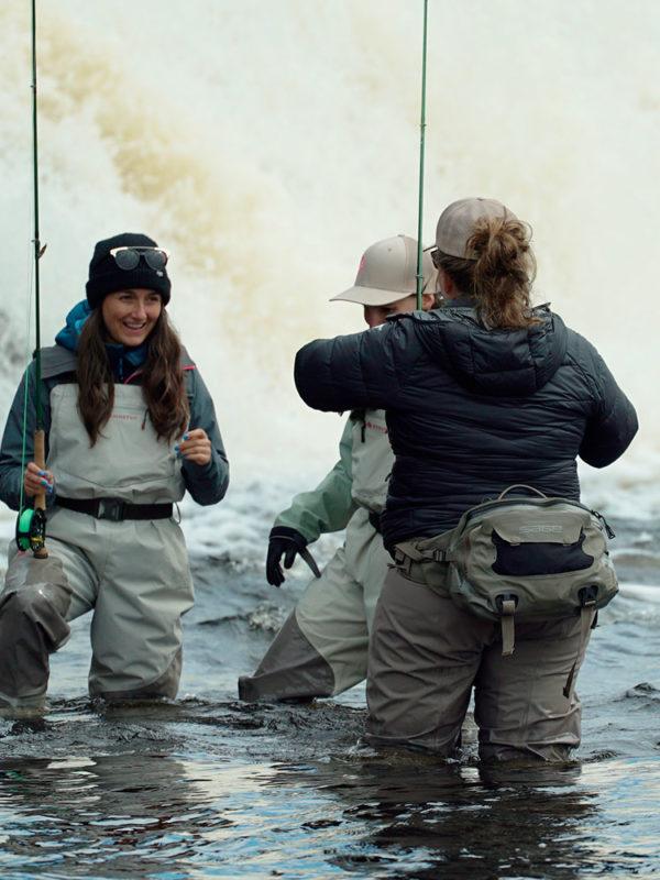 Des femmes pêchent à la mouche les 2 pieds dans une rivière au pied d'une cascade.