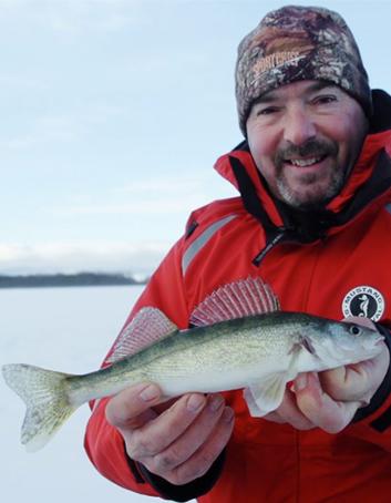 Un pêcheur montre un doré qu'il vient de pêcher sur la glace