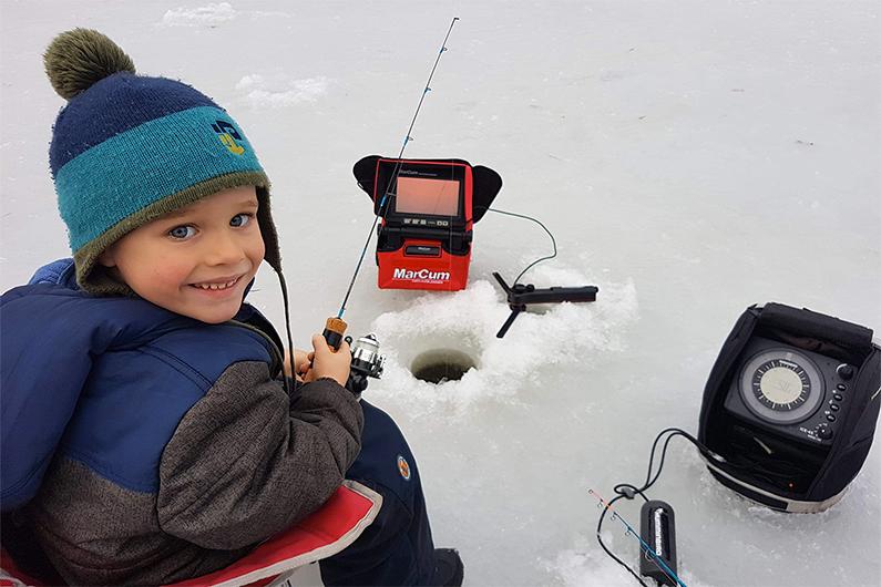 Petit garçon en train de pêcher sur la glace, une canne à pêche à la main.