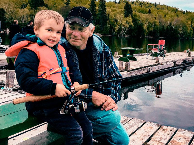 Un grand-père initie fièrement son petit-fils à la pêche lors de la Fête de la pêche.