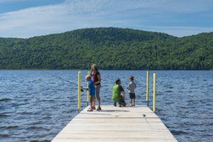 Des parents montrent à leurs jeunes enfants à pêcher à partir d'un quai.