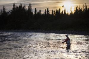 Un pêcheur à la mouche s'élance dans un lac , de l'eau jusqu'à mi-cuisse.