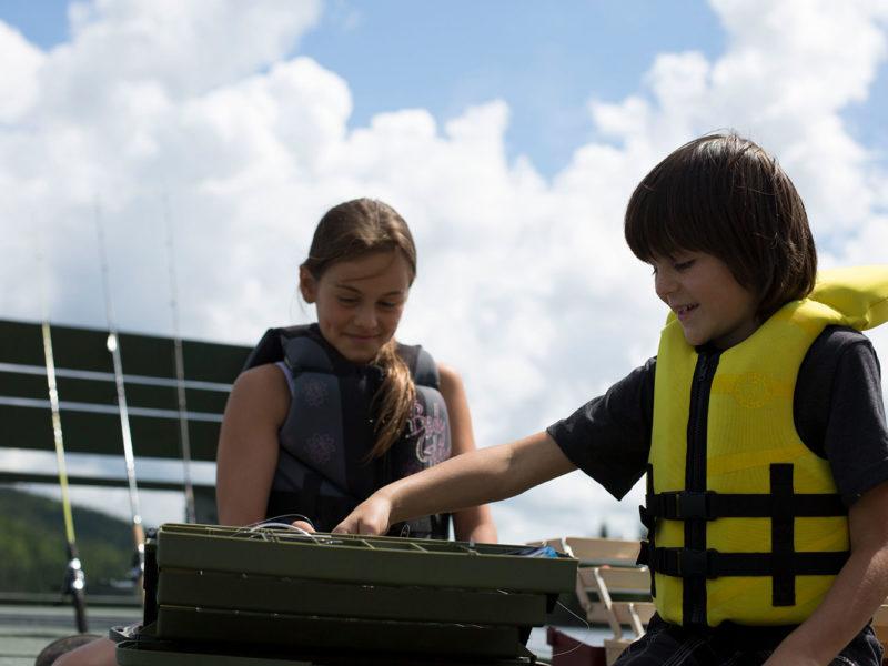 2 enfants fouillent dans leur coffre à pêche à la recherche du meilleur leurre.
