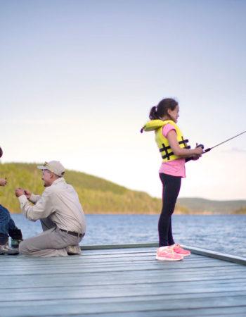 Un homme initie deux enfants à pêcher et à préparer leur équipement.