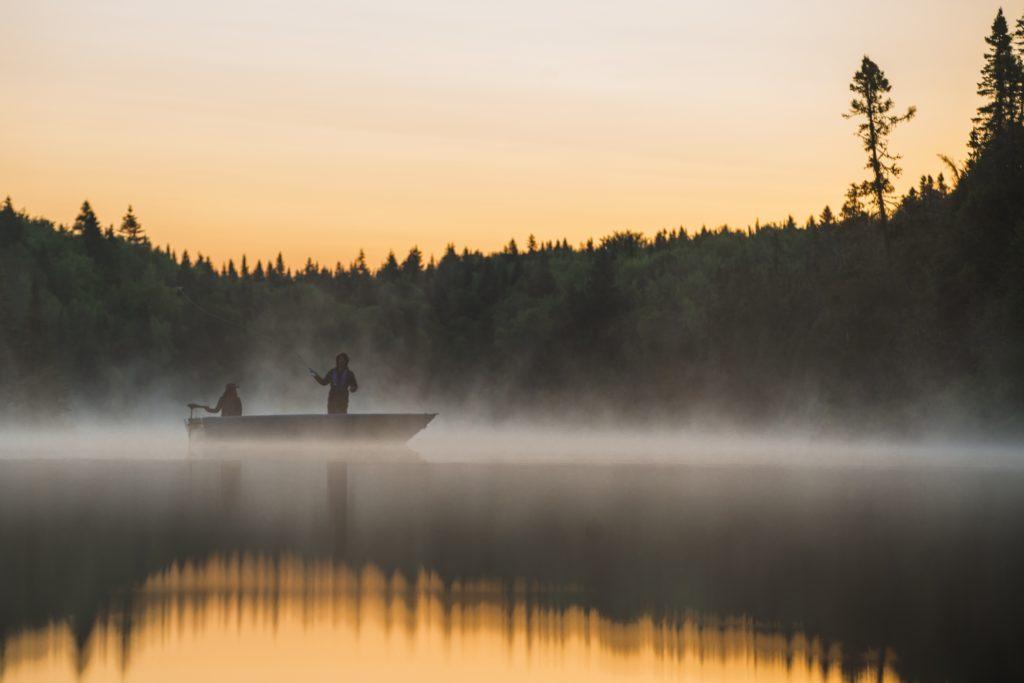 2 pêcheurs dans une embarcation lancent leur ligne au lever du soleil