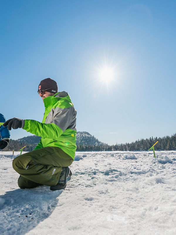 Un pêcheur montre à son fils à pêcher sur la glace à l'aide d'une brimbale.