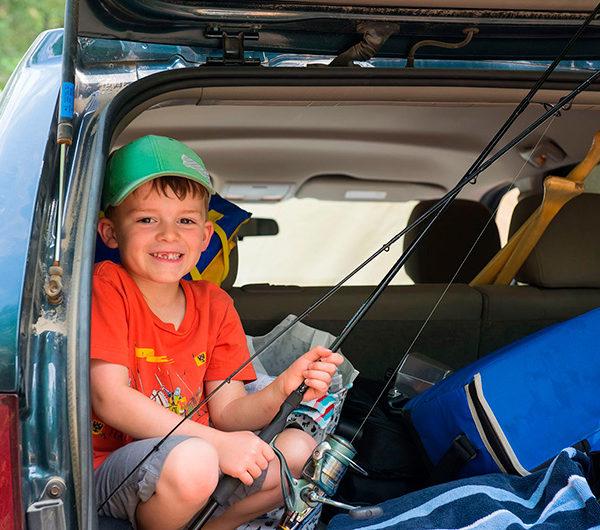 Un jeune enfant prépare sa canne à pêche bien installé dans le coffre arrière ouvert de la voiture.