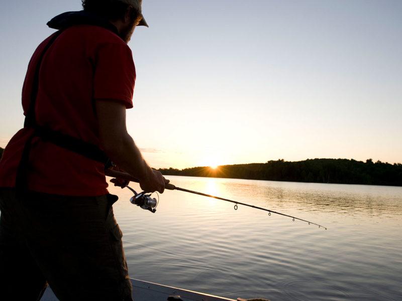 Un homme pêche debout sur un quai au crépuscule.