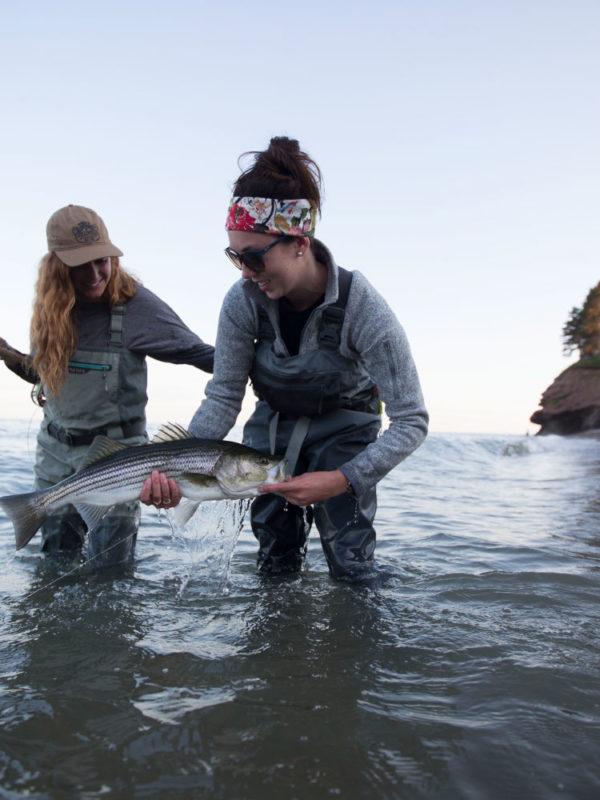Une pêcheuse à la mouche sort de l'eau un gros poisson sous l'oeil attentif de son amie.