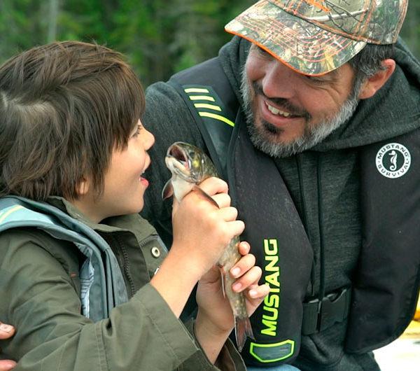 Un jeune pêcheur montre fièrement à son père la truite qu'il vient d'attraper.