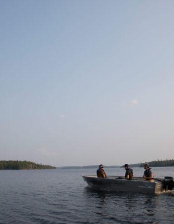Trois pêcheurs en chaloupe s'éloignent au large à la recherche du meilleur spot de pêche.